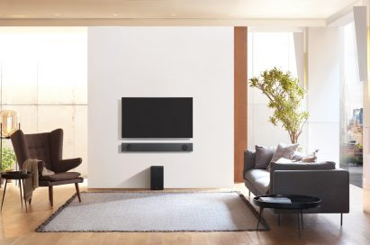 A direct view of the LG Soundbar model SL9YG installed on the wall below an LG TV, with the LG Wireless Rear Speaker Kit model SPK 8 on the floor below