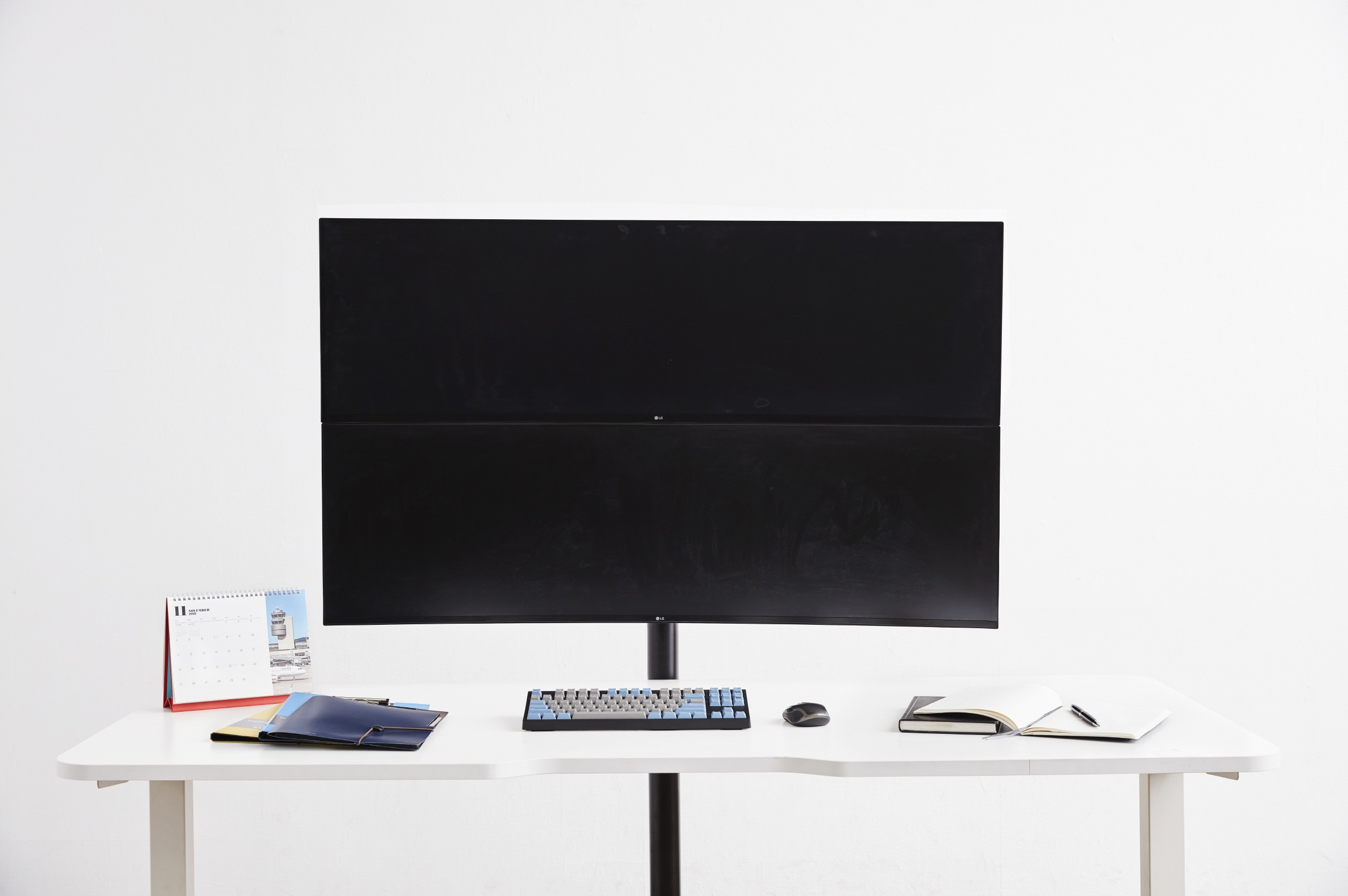 Front view of the LG UltraWide monitor model 49WL95 with office supplies sitting on a desk