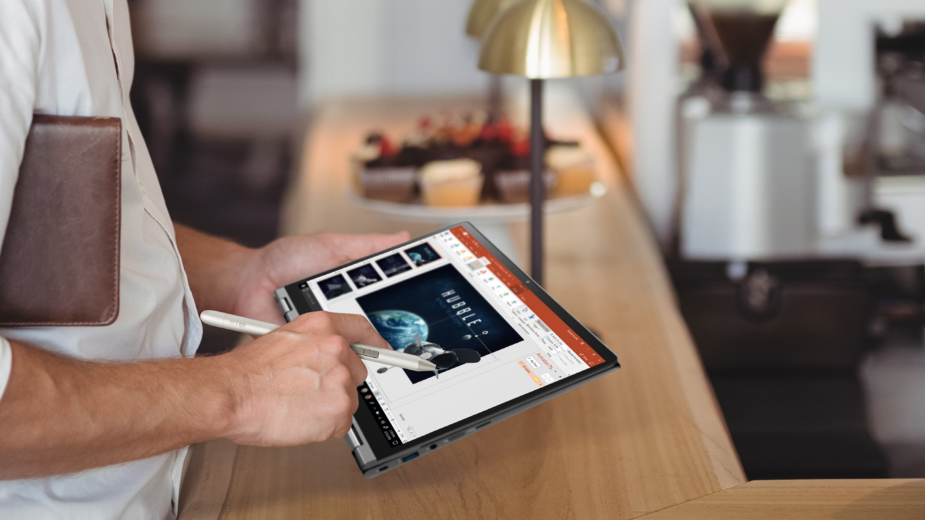 A close-up of a man touching the display of LG gram while making a presentation for work