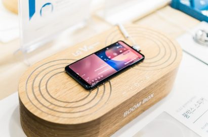 An LG V40 ThinQ is on display at a promotional zone, demonstrating its powerful amplification when placed on a solid surface or box.