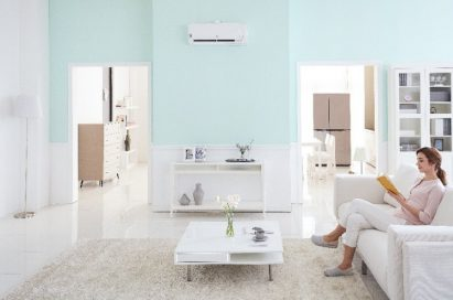 A woman on the sofa enjoys the enhanced indoor air quality thanks to LG's DUALCOOL air conditioner, which detects and eliminates tiny airborne particles such as PM1.0.