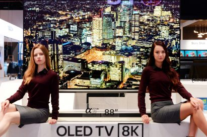 Two female models pose on the promotional stand of LG's 88-inch 8K OLED TV at LG's CES booth.