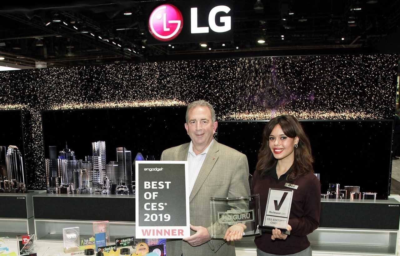 LG representatives pose with awards from Engadget, HD Guru and Reviewed.com