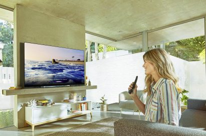 A lady watching the LG OLED TV with LG ThinQ AI at her home