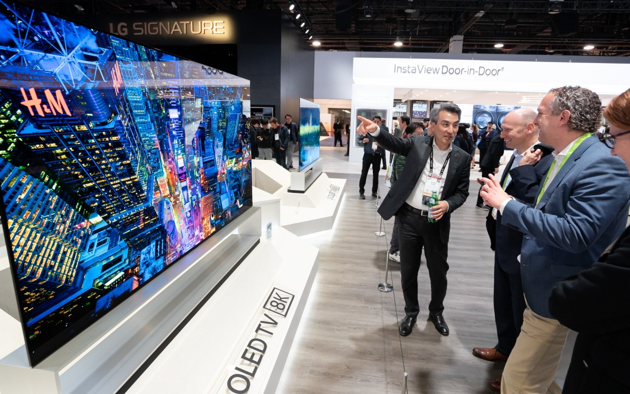 Side view of the display zone of LG's 8K OLED TV, the TV is to the left and a group of attendees on the right admire its excellent features.