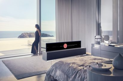A view of the LG OLED TV R's Line view while positioned at the end of a bed, with a woman leaning against a large window in the background