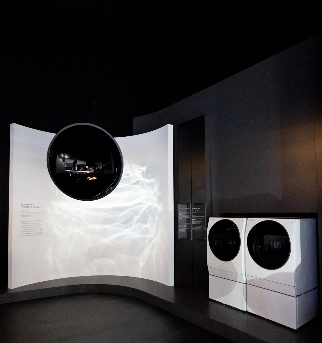 View of a pair of the LG SIGNATURE washer-dryers and a display to the left giving information about their features.