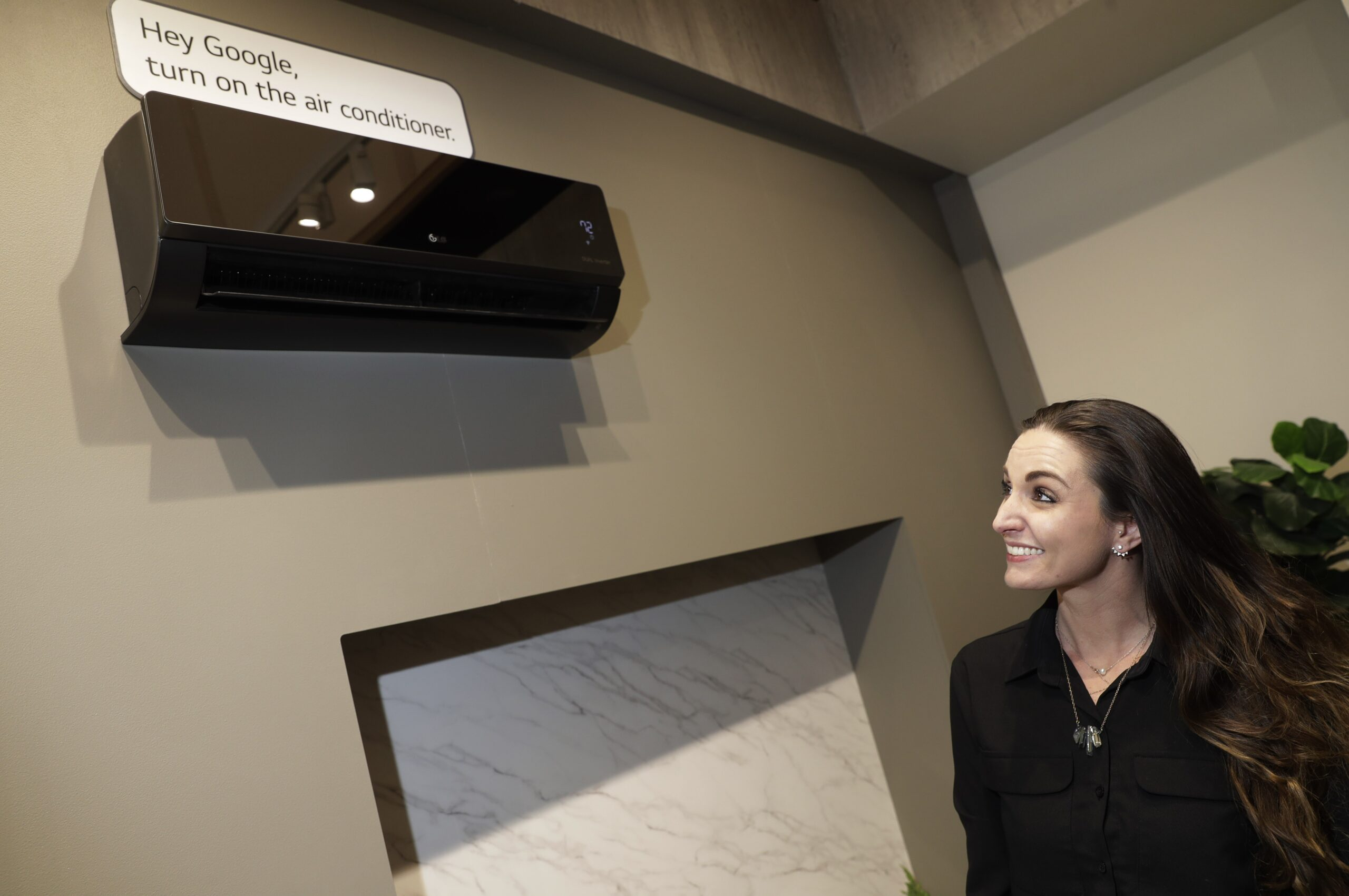 """Woman looking up at a black LG air conditioner with a sign that says """"Hey Google, turn on the air conditioner"""""""