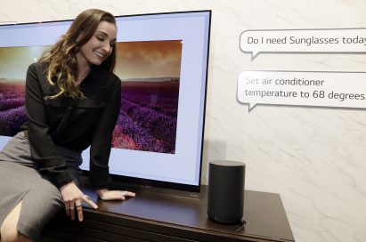 "Woman sitting in front of an LG TV while facing the LG AI speaker and asking, ""Do I need Sunglasses today?"" and, ""Set air conditioner temperature to 68 degrees"""