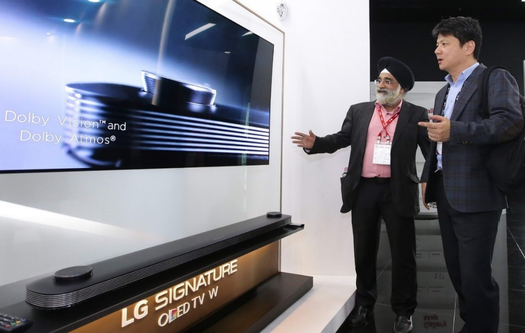 Two attendees discuss the Dolby Vision and Dolby Atmos technologies implemented in LG SIGNATURE OLED TV W.