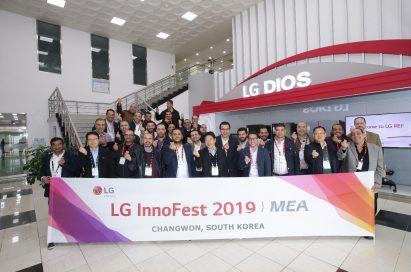 A group photo of attendees standing behind the wide LG InnoFest 2019 MEA banner
