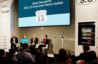 LG's large display hangs against the wall over the podium for a panel discussion during the Road to ATSC 3.0 exhibit event.