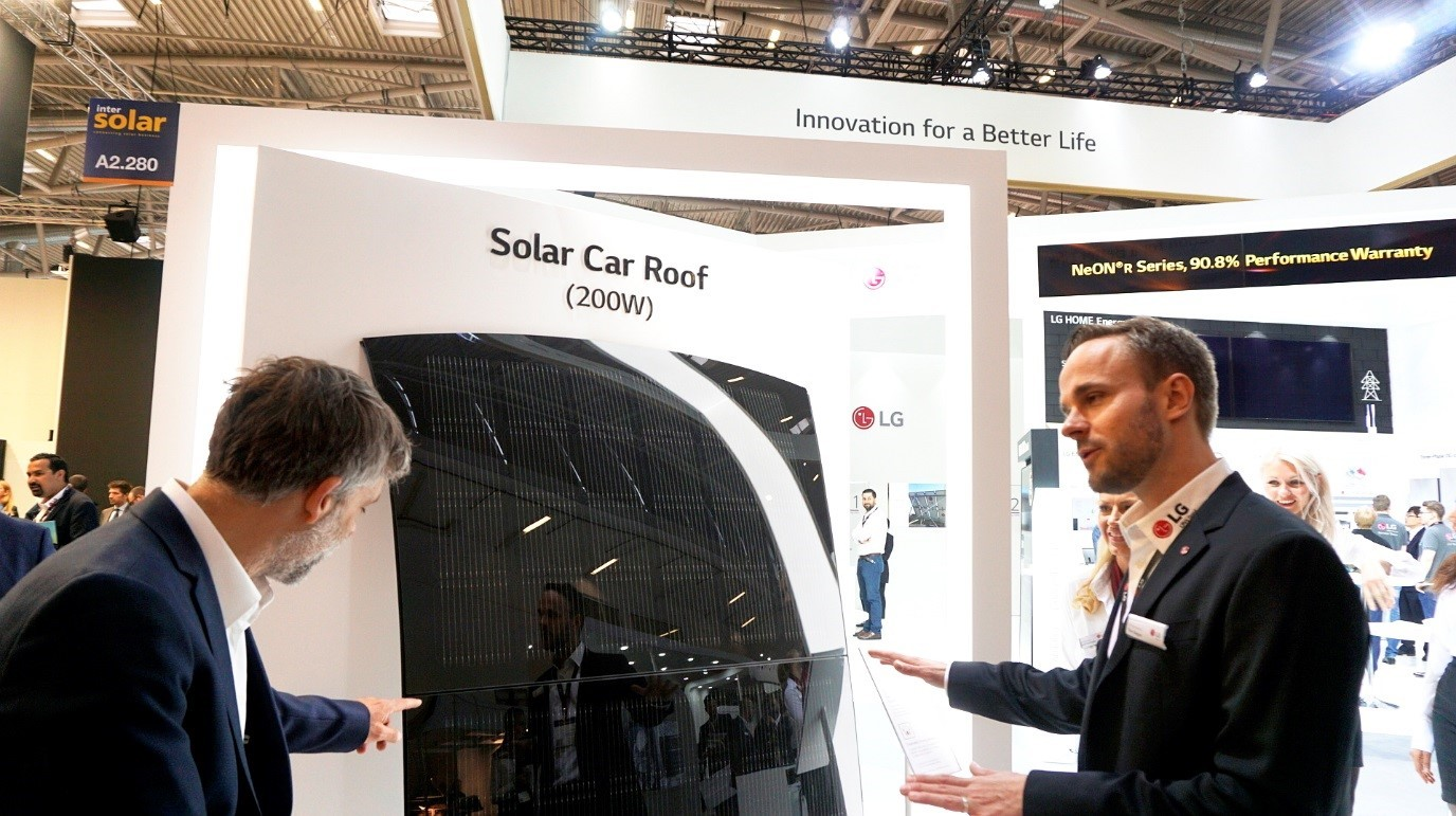 A male attendant explains the main features of LG Solar Car Roof to a visitor at its Intersolar Europe booth.