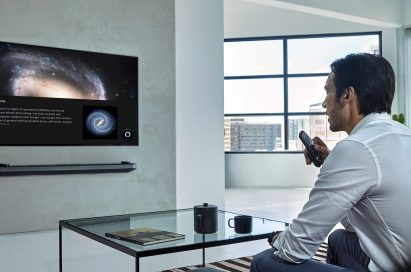 A man is watching LG TV supporting Amazon Alexa while holding the remote in one hand at home