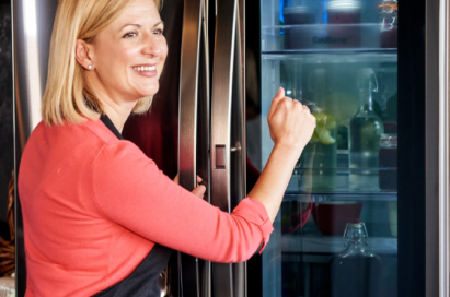 A lady in red shirts knocks on the transparent display panel of the LG InstaView Door-in-Door® refrigerator.