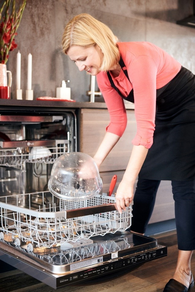 A lady in red shirts uses the LG QuadWash dishwasher to wash a transparent cooking bowl.