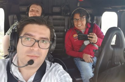 A selfie of three people in the helicopter taken by the pilot