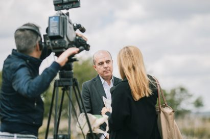 A project representative gives an interview with a local broadcast media.