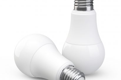 One LED light bulb laid down in front of an identical LED light bulb standing upright