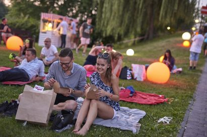 A couple look to be having fun as they open their food boxes at the LG Sunset Cinema event