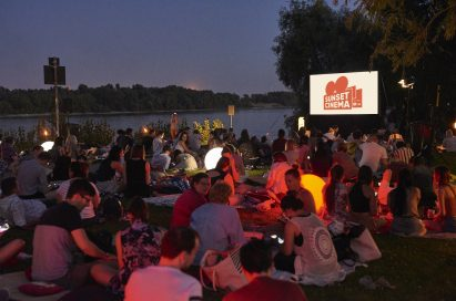 Audiences sit on the picnic mats at the nightfall and chatter before the movie starts