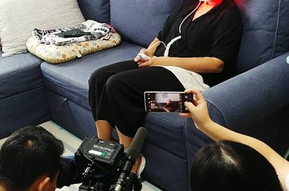 A cameraman shoots a video of a consumer sitting on the couch while wearing the LG Pra.L Derma LED Mask on her face.