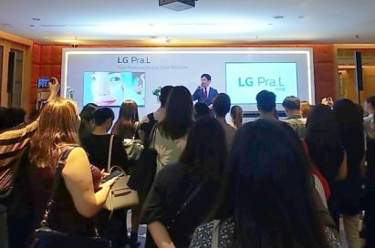 A presenter onstage explains the product lineup of the LG Pra.L in front of attendees.