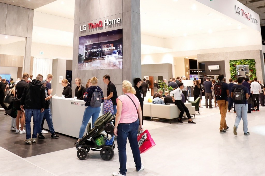 The LG ThinQ Home zone at IFA 2019 seen from a slight angle, there are many visitors looking around the booth.