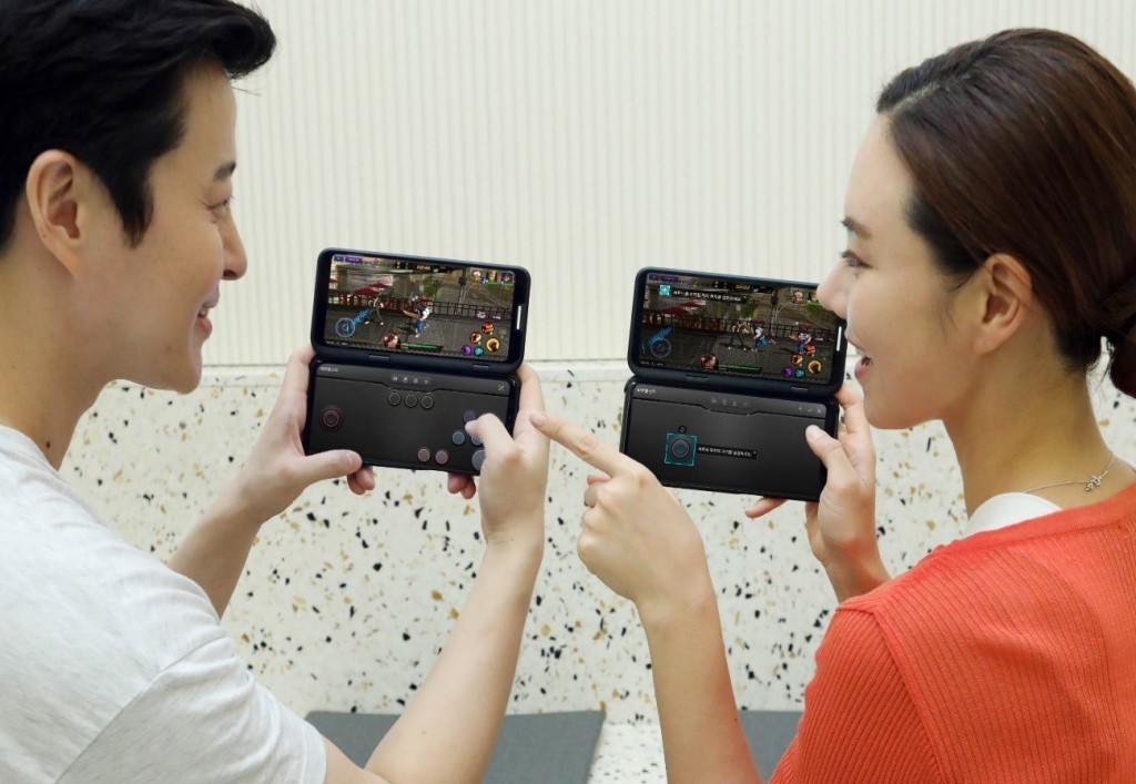 A man and a woman hold up the LG G8X ThinQ Dual Screen smartphones to play a multi-platform game at the same time.