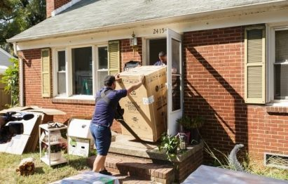 Two volunteers bring LG-donated home appliance into a house of Charlotte's Druid Hills neighborhood.