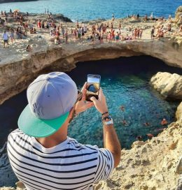 A male Instagram influencer shoots a video of the coast with his LG smartphone while people enjoy the beautiful weather.