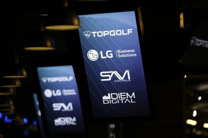 LG's commercial displays show four brand logos including LG Electronics and Topgolf Entertainment Group on their screens.