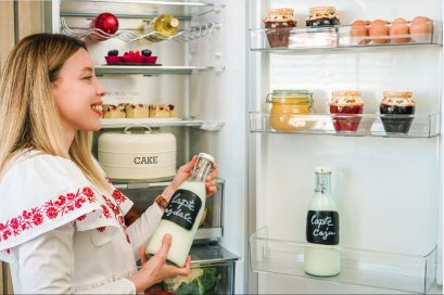 A look inside the LG refrigerator's interior as a woman poses with a bottle of milk after taking it from one of the door's shelves.