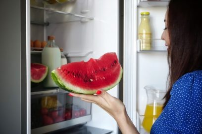 A woman takes a few bites of a slice of watermelon she just took out of the LG refrigerator.