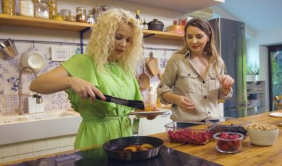 Two women prepare healthy dishes in a kitchen with food from the LG refrigerator.