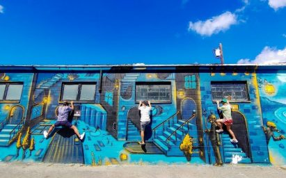 A photo taken by LG G8X ThinQ of three children scaling the side of a building decorated with colorful blue and yellow graffiti.