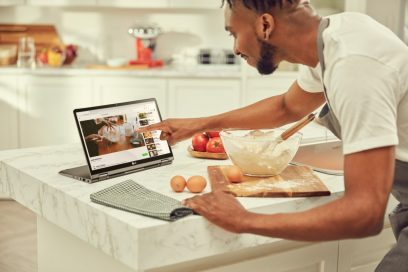 A man pointing at his LG gram model 14T90N's display while following a cooking demonstration video as he prepares his food