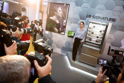 Fashion designer Tamara Falcó poses next to LG SIGNATURE Wine Cellar and her movie-inspired artwork as numerous reporters take photos.