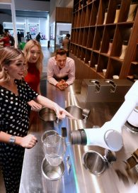 Visitors to the 'ClOi's Table' restaurant watch on as one of LG's CLOi CoBots prepares their meal
