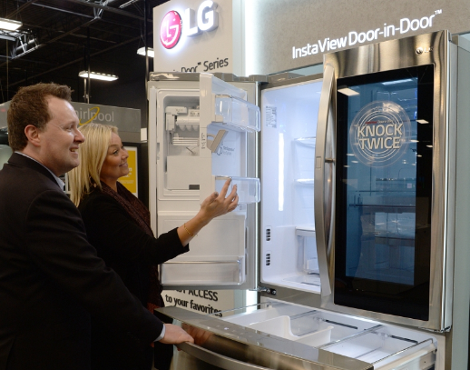 A man and woman take a closer look at the technology found inside the LG InstaView Door-in-Door refrigerator by opening its fridge door compartment