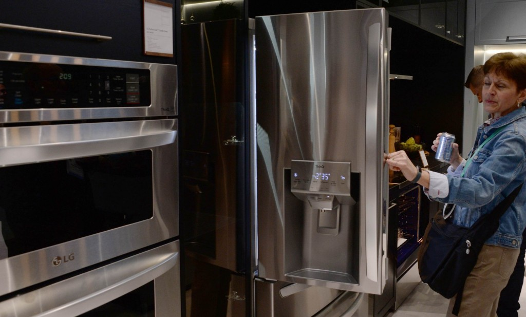 A visitor to the LG booth opens one of the company's advanced refrigerators while looking toward the innovative oven range which is on display to its side