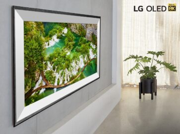 A closer look at LG's 77-inch 8K OLED TV model ZX hanging flush on a living room wall, with the LG OLED Real 8K logo in the top-right corner