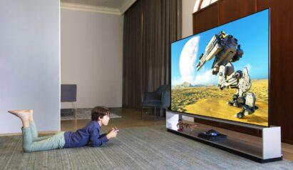 A boy enjoying the big-screen gaming experience on LG 8K OLED TV model ZX as he lays on a cozy living room floor