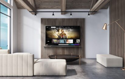 A view of an LG TV hanging on the wall of a wide modern living room as it displays the Apple TV app