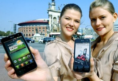 Two women pose with the LG Optimus 2X