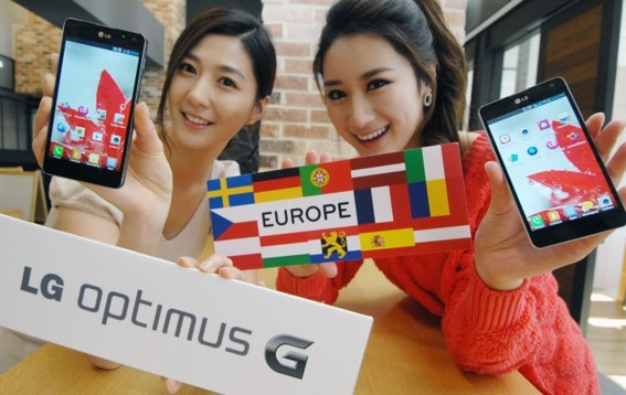 Two women show off LG Optimus G while holding up many European flags