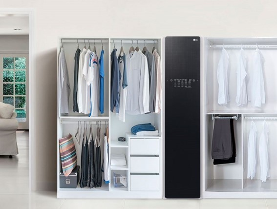 The LG Styler is placed in a room between two white open wardrobes full of clothes