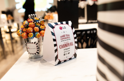 A sign for the LG gram Carnival stands on a table next to an LG-branded pot filled with lollipops