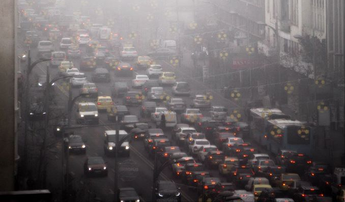 Hundreds of vehicles sit in heavy traffic within a bustling city, while surrounded by heavily polluted air