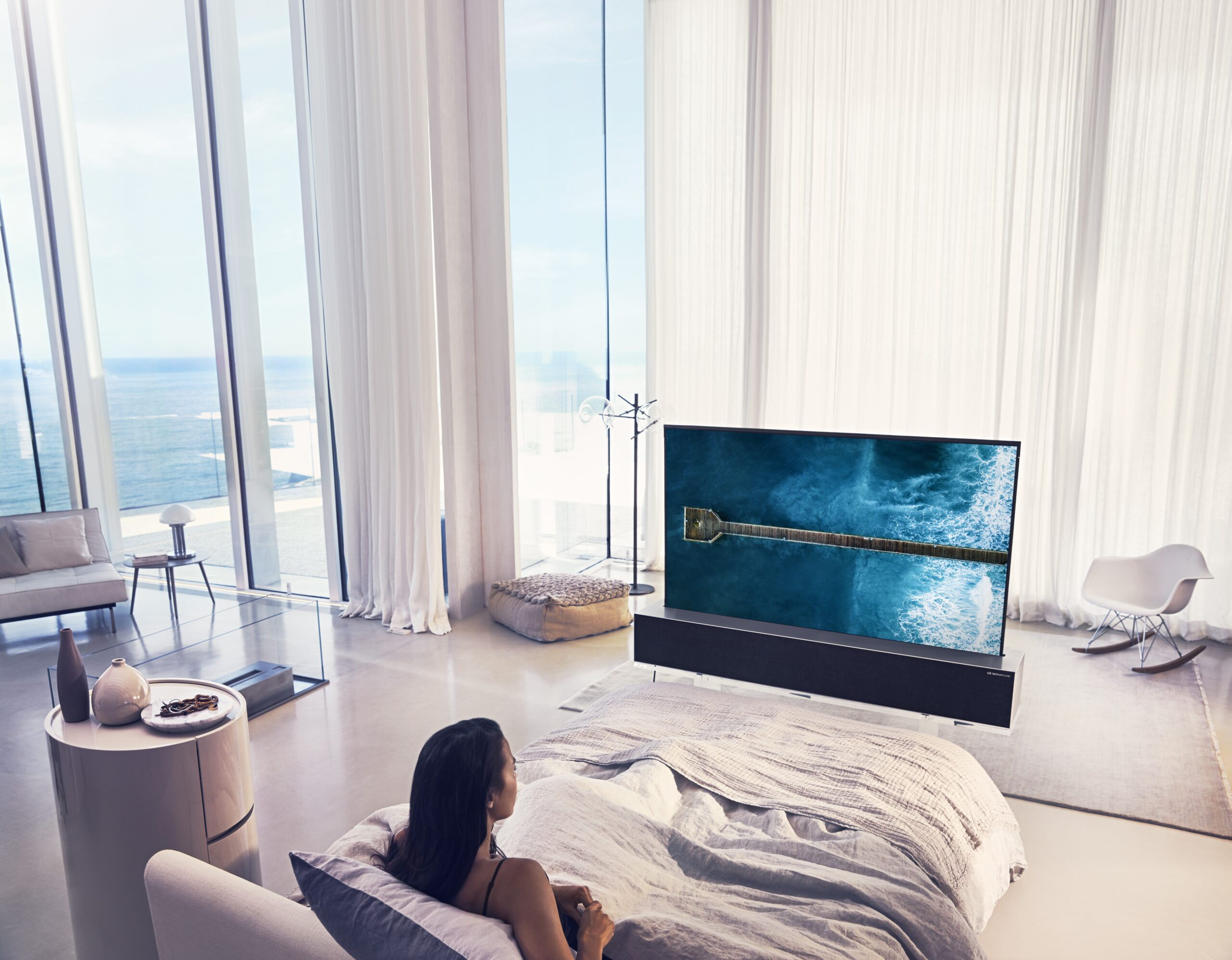 A woman in bed watching an LG SIGNATURE OLED TV R at a bright, beachside mansion.
